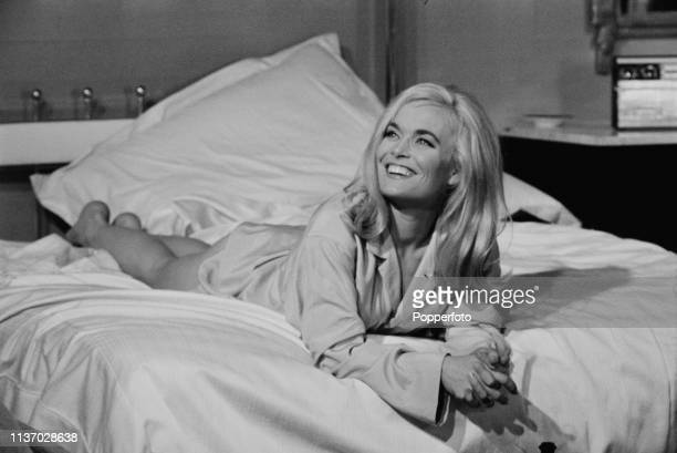 English actress Shirley Eaton pictured in character as Jill Masterson lying on a bed wearing a pale blue shirt on the set of the James Bond film...