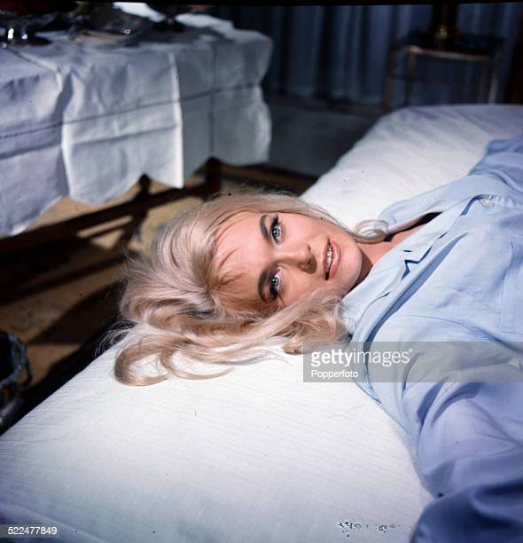 English actress Shirley Eaton posed lying on a bed wearing a light blue shirt on the set of the James Bond film 'Goldfinger' at Pinewood Studios in...