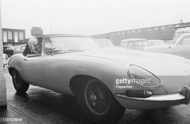 English actress Shirley Eaton who currently plays the character of Jill Masterson in the James Bond film 'Goldfinger' pictured seated in the driver's...