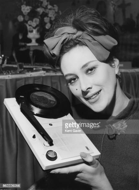 English actress Sue Lloyd admires a Takt a miniature portable record player from Japan at London's first International Fancy Goods Exhibition...