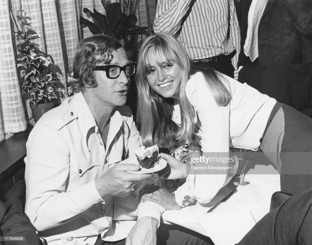 English actress Susan George hands a slice of cake to actor Michael Caine at her 21st birthday party, 27th July 1971. She is celebrating the occasion at Twickenham Studio, where she is working on her latest film, 'Straw Dogs'.