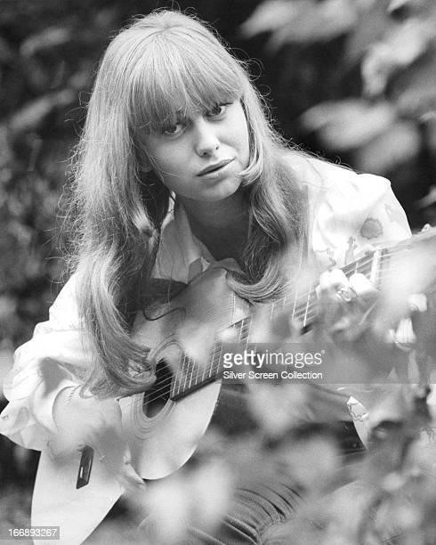 English actress Susan George playing an acoustic guitar circa 1970