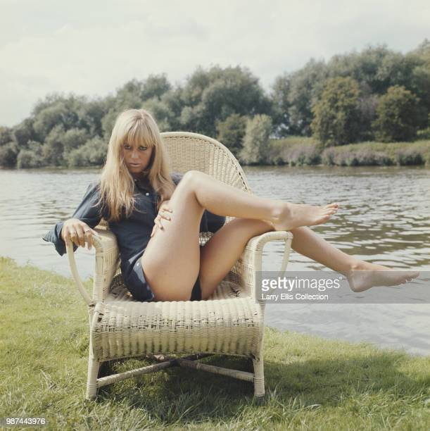English actress Susan George posed wearing a blue blouse seated on a wicker chair beside a river in England in 1972