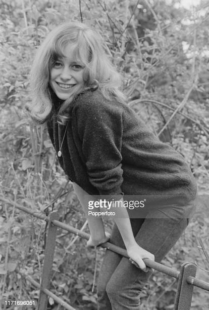 English actress Susan George, who appears in the television soap opera Weavers Green, stands on a metal fence in June 1966.