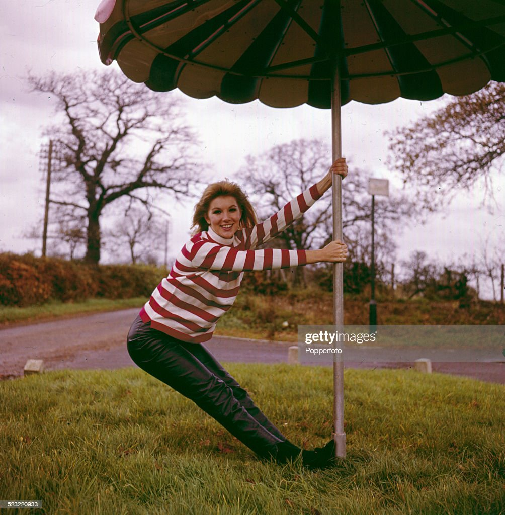 English actress Susan Hampshire posed wearing a red and white striped jumper and leather trousers whilst holding a large patio umbrella in 1964.