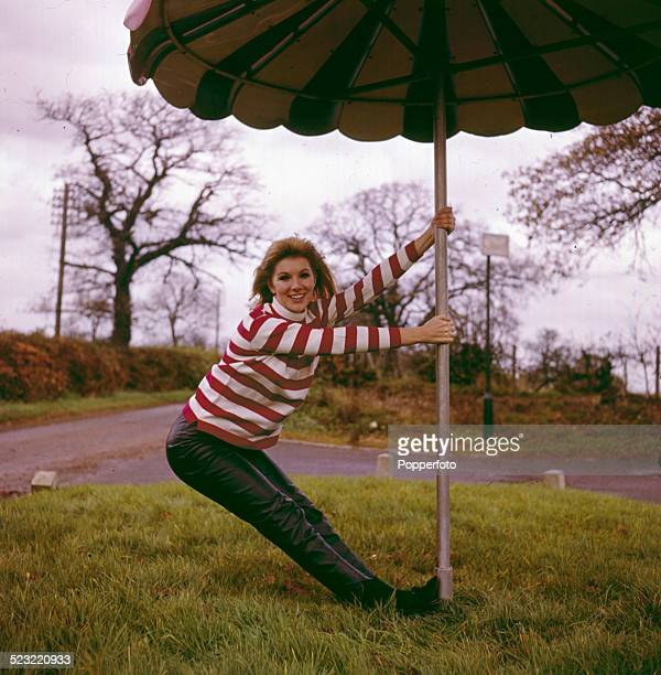 English actress Susan Hampshire posed wearing a red and white striped jumper and leather trousers whilst holding a large patio umbrella in 1964