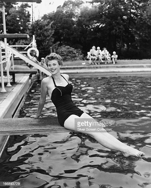English actress Susan Stephen posing on a diving board at a swimming pool, circa 1955.
