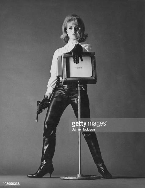 English actress Suzy Kendall poses with a gun and an autocue with the word 'Shoot' on it 29th October 1963