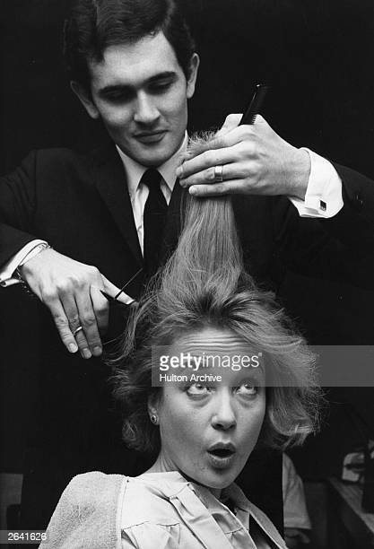 English actress Sylvia Syms having her hair cut in preparation for her role as Peter Pan in London's Scala Theatre pantomime. Her hair is being cut...