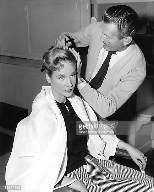 English actress Sylvia Syms having her hair styled, circa 1958.