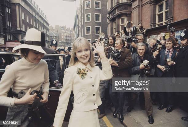 English actress Tessa Wyatt waves to reporters, photographers and members of the press as she arrives for her wedding to disc jockey and broadcaster...