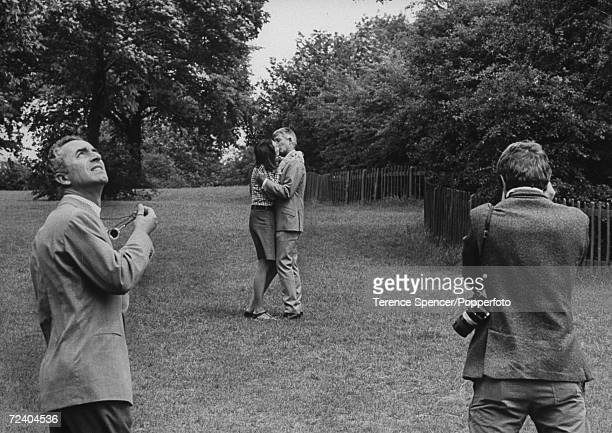 English actress Vanessa Redgrave, playing the role of Jane, kisses a man as David Hemmings, playing the photographer Thomas, takes pictures all under...
