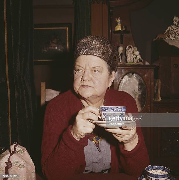 English actress Violet Carson who plays the character of Ena Sharples in the television soap opera Coronation Street drinks a cup of tea at home in...