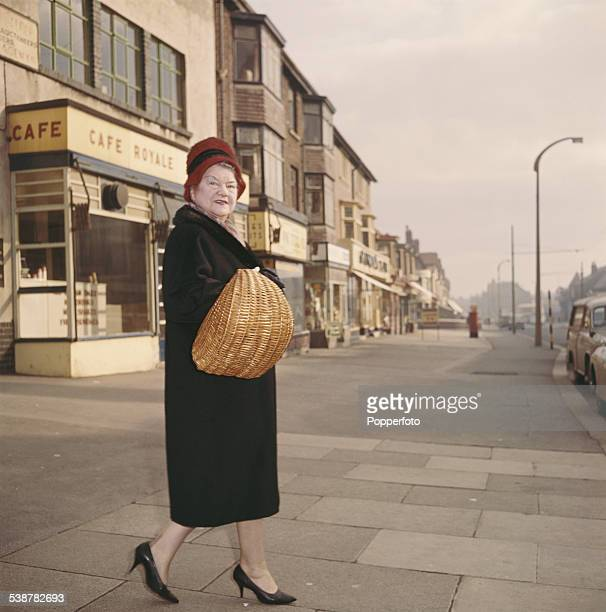 English actress Violet Carson who plays the character of Ena Sharples in the television soap opera Coronation Street walks down a street holding a...