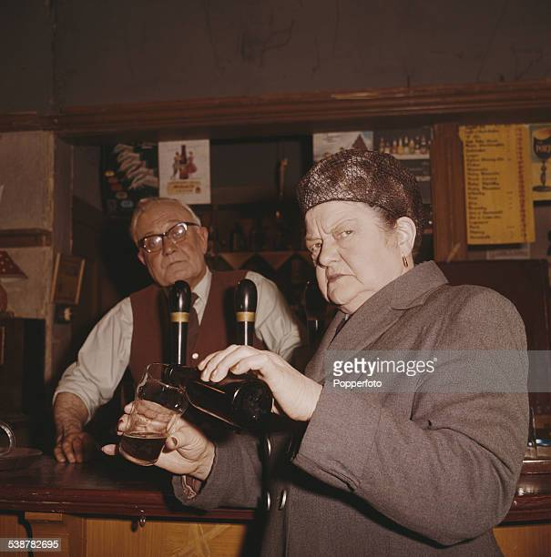 English actress Violet Carson who plays the character of Ena Sharples in the television soap opera Coronation Street pours a glass of milk stout from...