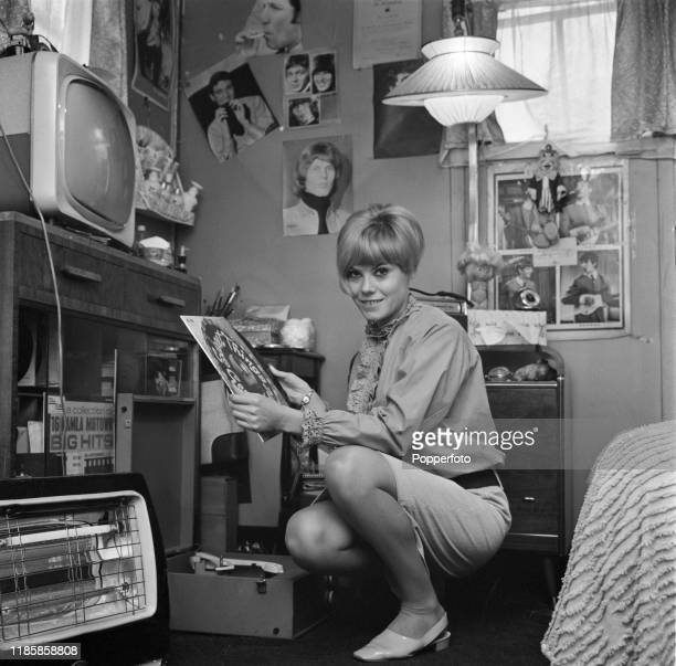English actress Wendy Richard posed playing records on a portable record player in her bedroom at home in September 1966