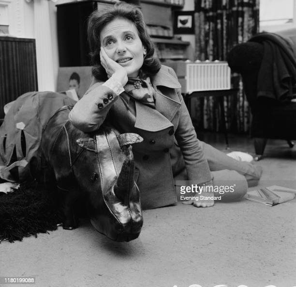 English actress Yvonne Mitchell sits on the floor near a stuffed rhinoceros UK 27th April 1970