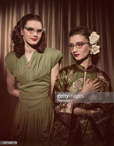 English actresses Josephine Stuart and Zena Marshall wear a green short sleeved dress with ruched central panel and Chinese style silk robe along...