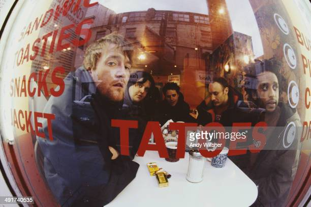 English alternative rock Elbow seen through a cafe window December 2000 Left to right singer Guy Garvey keyboard player Craig Potter guitarist Mark...