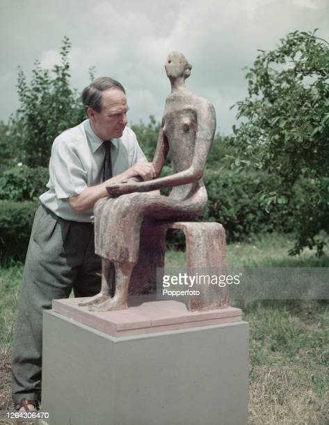 English artist and sculptor Henry Moore stands beside his sculpture 'Seated Figure', modelled in terracotta, in the garden of his home and studio, a...