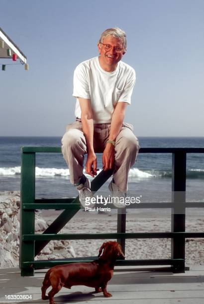 English artist David Hockney poses for a portrait with his dog on the terrace of his beach house in April 1991 in Malibu California
