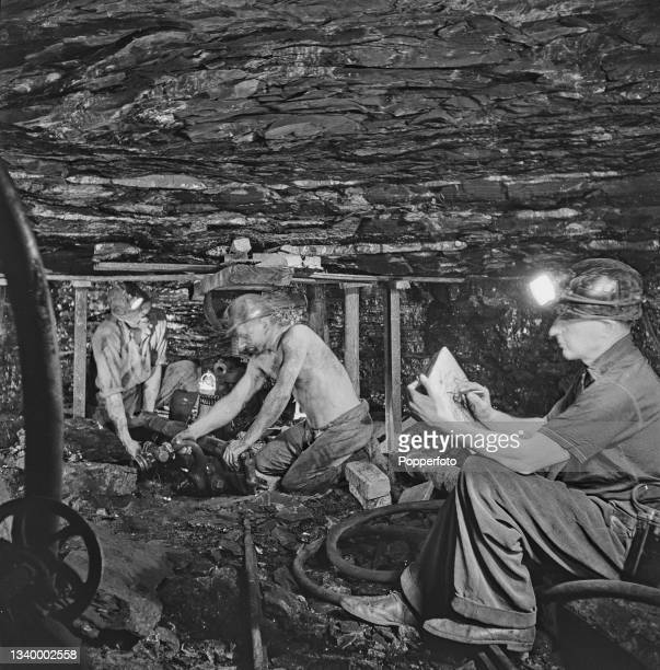 English artist Henry Moore makes sketches of miner Jack Hancock and a colleague at work on the bottom level of Wheldale Colliery, a coal mine in...