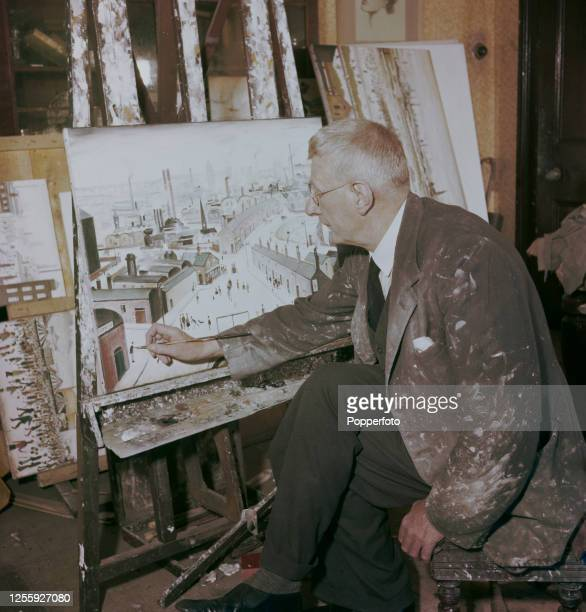English artist L S Lowry at work putting the finishing touches to a painting in the studio of his house in the village of Mottram in Longdendale near...