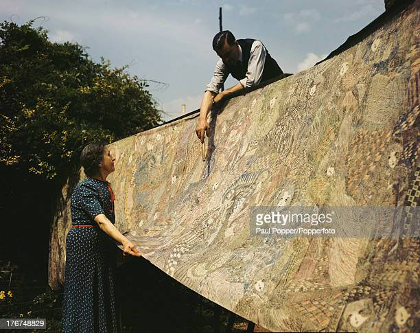 English artist Madge Gill and her son, Lawrence, hang her 1936 mural in her garden in East Ham, London, England, 18th August 1947. The vast work,...