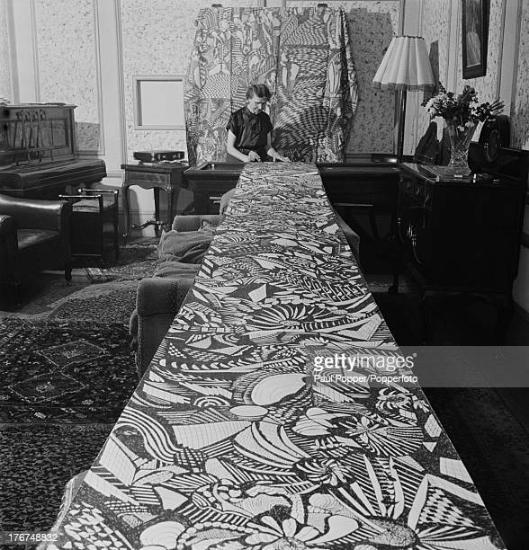 English artist Madge Gill displays a 15ft calico drape mural she has been working on at home, London, England, 18th August 1947. Once the mural is...