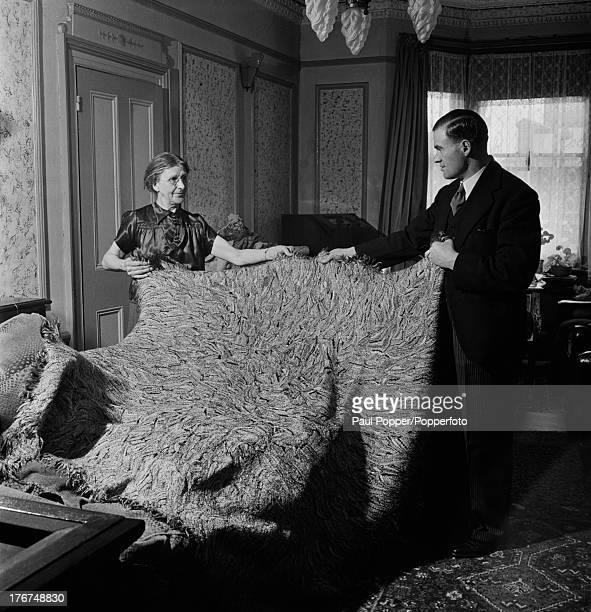 English artist Madge Gill in her East Ham home displays a rug she has made by inserting left over strands of silk into a canvas backing, London, 19th...
