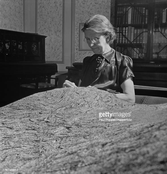 English artist Madge Gill making a rug at home by inserting left over strands of silk into a canvas backing, East Ham, London, England, 19th August...