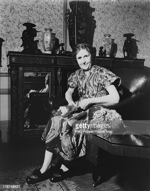 English artist Madge Gill netting with fine silks whilst wearing one of her own creations embroidered in coloured wools at home in East Ham, London,...