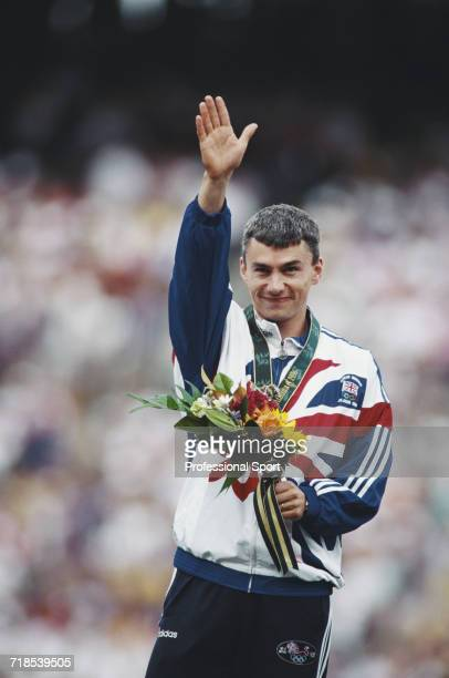 English athlete Jonathan Edwards raises one arm in the air in celebration on the medal podium after finishing in second place to win the silver medal...