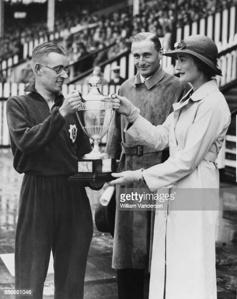 English athlete Lord Burghley later the 6th Marquess of Exeter and Lady Burghley present a trophy to Sydney Wooderson at White City London 11th July...