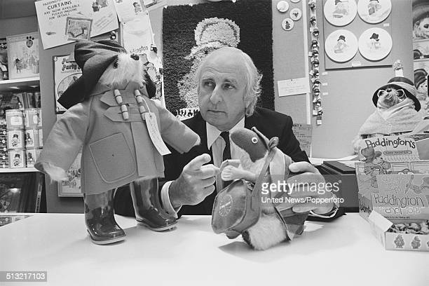 English author and creator of the Paddington Bear series of books Michael Bond posed with a model of Paddington Bear in London on 18th June 1980