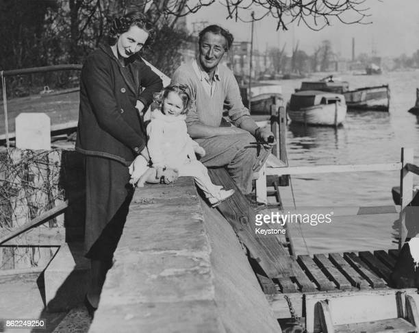 English author and MP Alan Patrick Herbert in his garden on the banks of the River Thames in Hammersmith, west London, with his daughter Crystal, the...