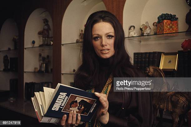 English author and novelist Jackie Collins pictured holding a copy of the book 'Sinatra A Biography' in London in 1968