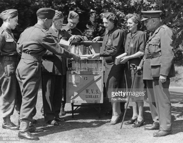 English author Barbara Cartland assists with the running of the WVS library during World War II, circa 1943.