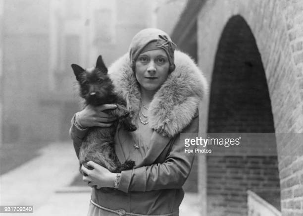 English author Barbara Cartland , the wife of Alexander McCorquodale, with her dog, December 1928.