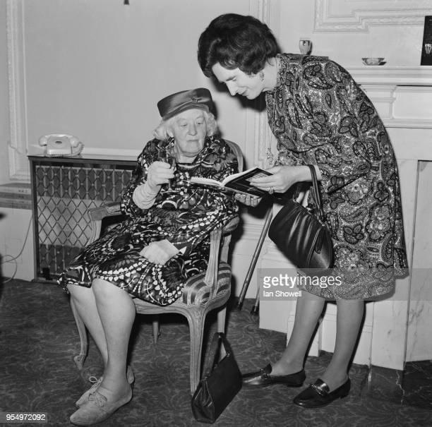 English author Dawn Langley Simmons shows a copy of her book 'Man Into Woman' to her adoptive mother actress Dame Margaret Rutherford during the...