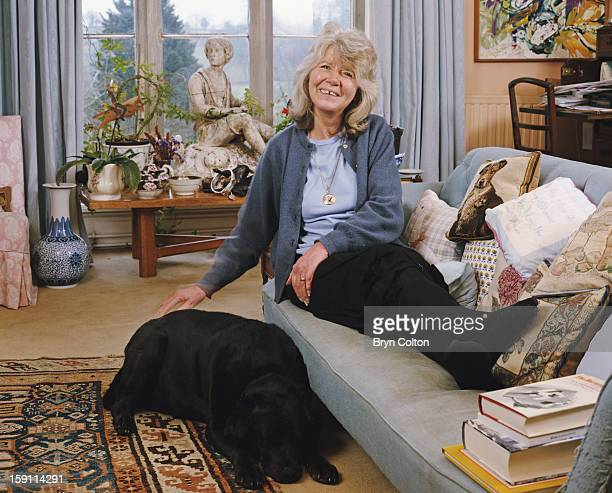 English author Jilly Cooper with a pet labrador at her home in Bisley, Gloucestershire, 4th February 2000.