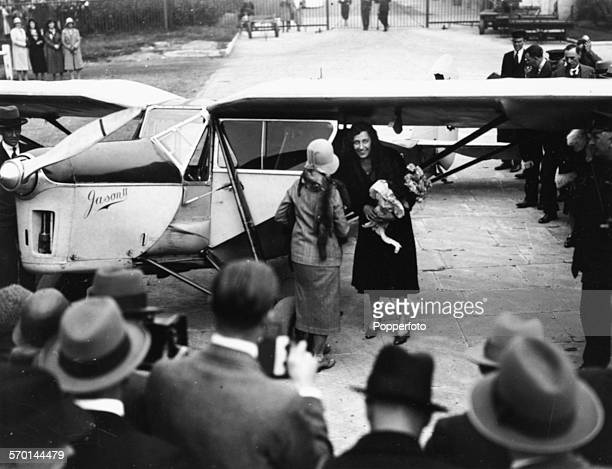 English aviator Amy Johnson is greeted by crowds and a bouquet of flowers as she arrives at Croydon Airport in South London after her return flight...