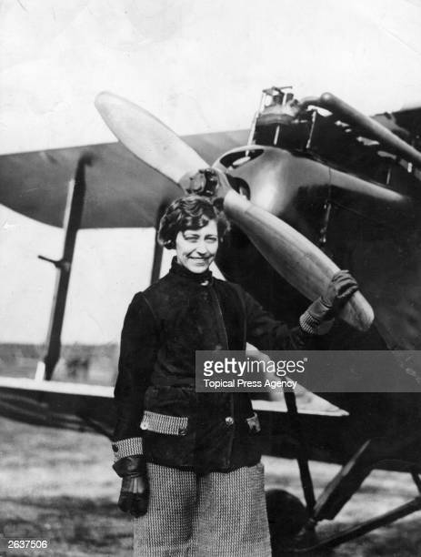 English aviator Amy Johnson standing by the propeller of her DH Gipsy Moth plane 'Jason' in which she made her record solo flight to Australia in...