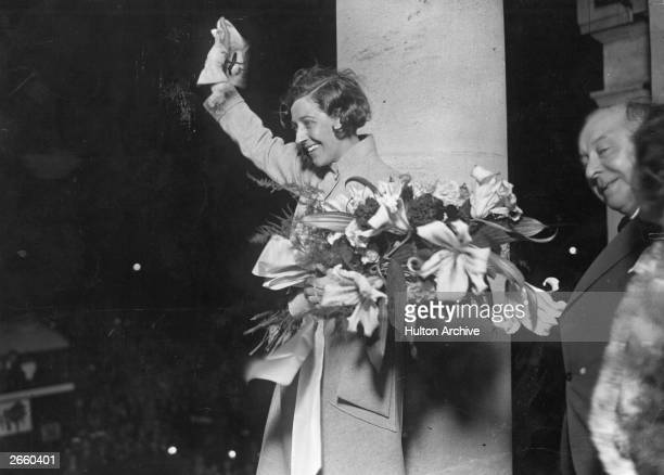 English aviator Amy Johnson waves to a crowd of wellwishers outside Grosvenor House on her return to London following her solo flight to Australia