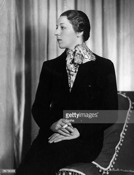 English aviator Amy Johnson wearing a woollen suit from the collection of flight clothes designed for her by Madame Schiaparelli for her solo flight...