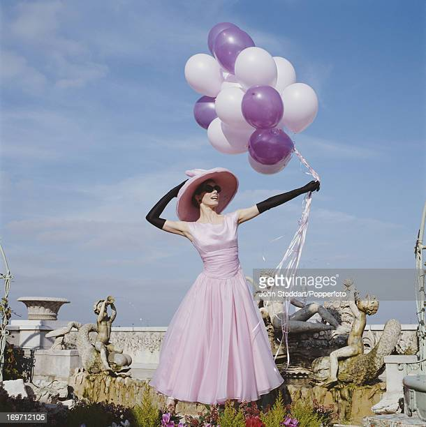 English ballerina Darcey Bussell poses in a pink dress with balloons circa 1997