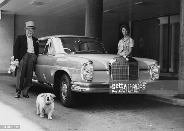 English bandleader and impresario Jack Hylton leaves London for the Epsom races in his turquoise Mercedes Benz 220 SEC coupé with his daughter...
