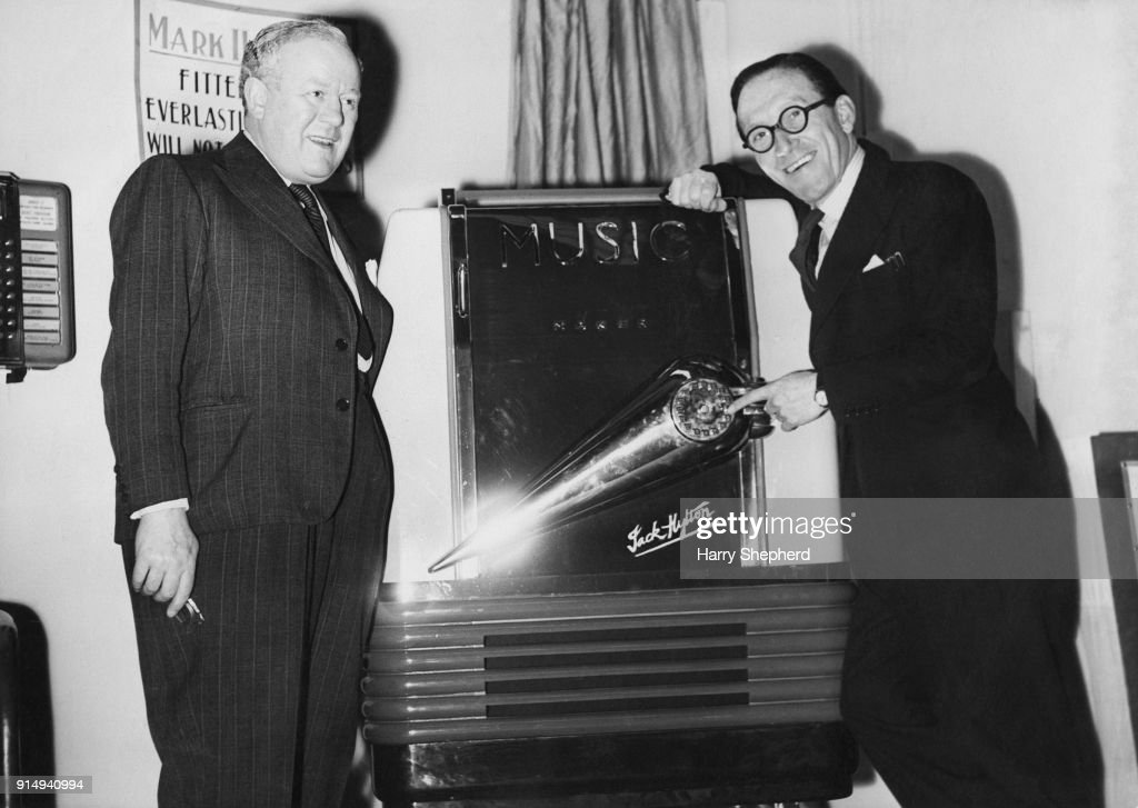 English bandleader and impresario Jack Hylton (1892 - 1965, left) with comedian Arthur Askey (1900 - 1982, right) at the Amusement Exhibition at the Royal Horticultural Hall in London, where Hylton is introducing the jukebox or 'Music Maker' to the UK, 8th February 1946.