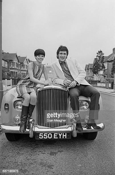 English bass guitarist for 'The Who' John Entwistle and Alison Wise on the bonnet of a Rolls Royce car 17th March 1967