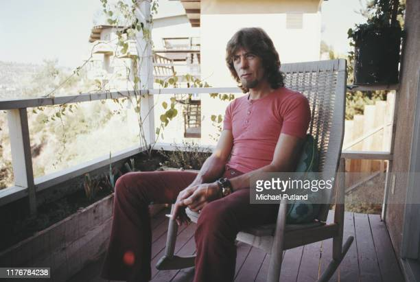 English blues singer and guitarist John Mayall seated on a rocking chair on the verandah of his house in Laurel Canyon, Los Angeles circa 1972.